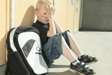 A very sad boy in school playground