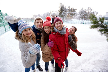 happy friends with smartphone on ice skating rink