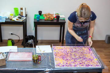 Woman painter makes pattern on water surface with inks