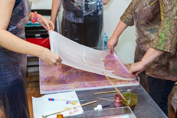 People putting silk fabric from water with inks for ebru drawing printing