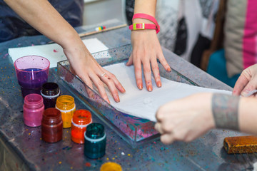 Women putting silk on water surface for color inks printing into silk, ebru art