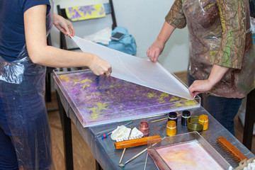 People printing ebru drawing from water surface into silk