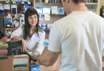 A Pharmacist helping customer at counter place