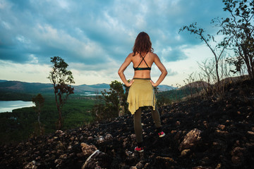 Woman standing on a scorched hill in a tropical climate