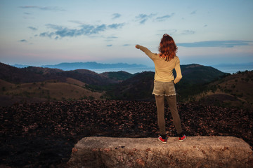 Woman standing on a rock is pointing