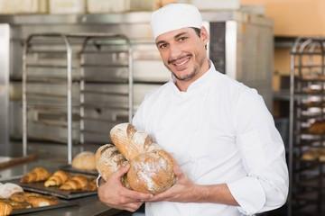 Baker holding freshly baked loaves