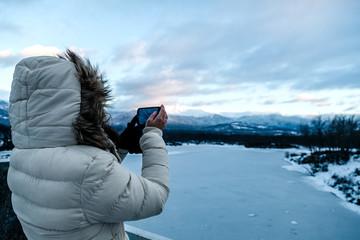 Woman Taking Photos of a Frozen Lake at Twilight