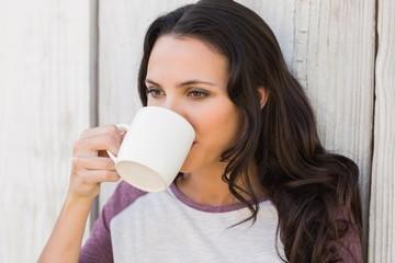 Pretty brunette drinking from mug