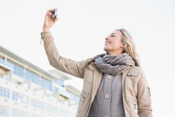 Smiling blonde posing and taking a selfie