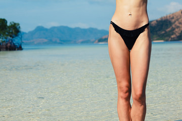 Belly and legs of woman standing on tropical beach