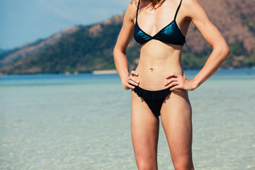 Slim young woman standing on tropical beach