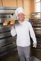Baker holding tray of fresh bread