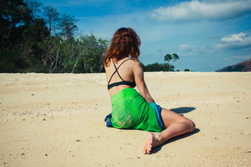 Woman in sarong sitting on tropical beach