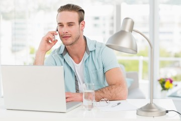 Focused businessman on the phone while using laptop