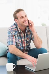 Smiling man on a phone with a laptop at home
