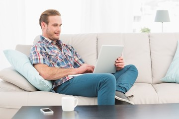Relaxed man sitting on sofa using laptop
