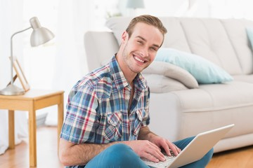 Smiling man sitting on the floor using laptop