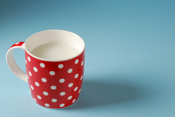 red cup of milk on a blue background