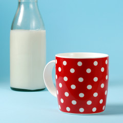 Still life with red cup of milk and antique bottle of milk