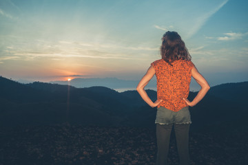 Woman watching sunrise over mountains