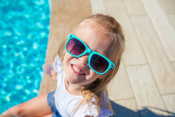 Portrait of adorable little girl have fun near swimming pool