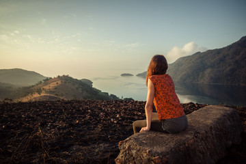 Woman sitting on unusual rock at sunrise
