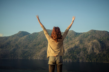Woman raising her arms on top of mountain