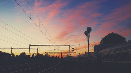 Sunset on the railway. Train on the beautiful sky background