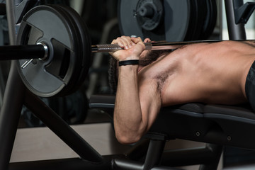 Young Man Exercising Chest With Barbell