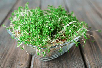 Fresh cress salad in glass bowl and wooden planks background