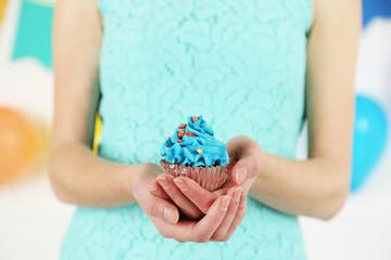 Woman holding beautiful cupcake, close up