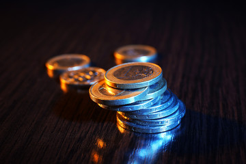 Heap of coins on wooden table background