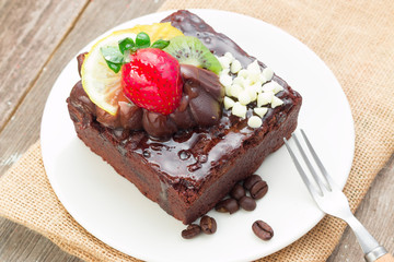 Piece of chocolate cake with icing and fresh berry on wooden bac