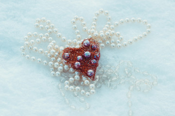 composition of beads and heart in the snow background edited