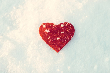 frozen red heart on snowy winter background edited