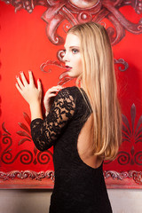 Misterious girl in black dress on red vintage wall