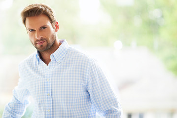 Goodlooking man in shirt standing against the window