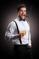 Young guy smoking cigar and drinking whiskey