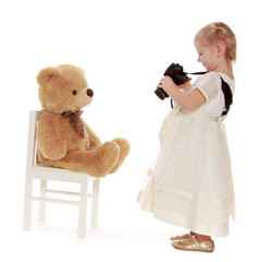 Clever little girl photographed his favorite teddy bear.