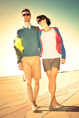 Romantic Young tourist couple standing on a beach at sunset