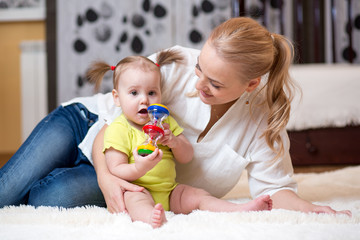mom and baby playing toy at home