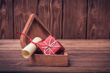 Rolled paper and gift box on Valentine's day over defocused vint