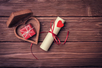 Rolled paper and gift box on Valentine's day over vintage wooden