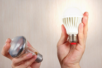 Hands compared incandescent bulb and glowing led lamp