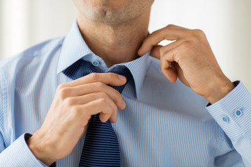 Wall Mural - close up of man in shirt adjusting tie on neck