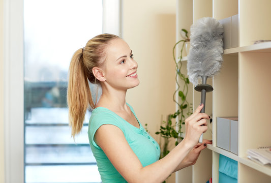 happy woman with duster cleaning at home