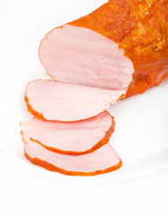 Large piece of ham with cut slices on plate, isolated on white b
