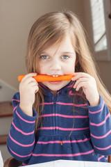little girl biting on a carrot