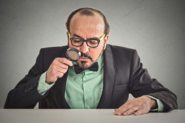 man sitting at desk looking through magnifying glass