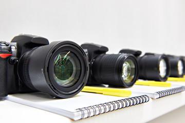 Reflex digital cameras dslr with notepad close-up